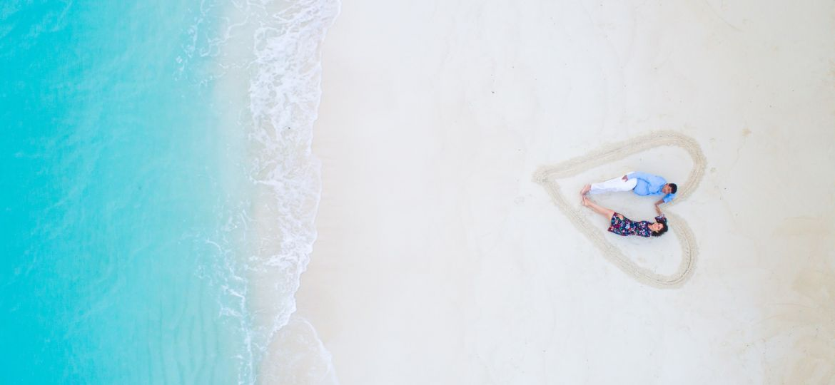 man-and-woman-lying-on-white-sand-near-sea-shore-1198839